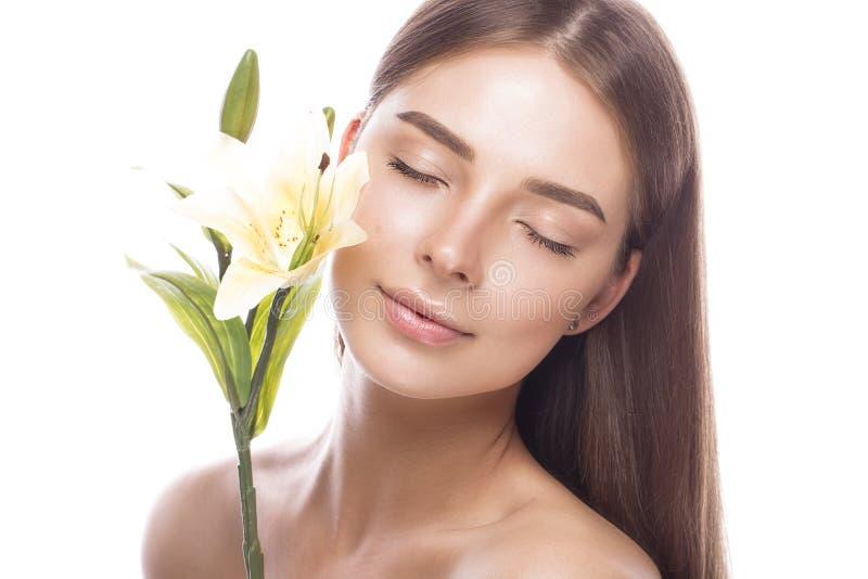 Den härliga unga flickan med ett ljust naturligt smink och gör perfekt hud med blommor i hennes hand Härlig le flicka royaltyfri foto