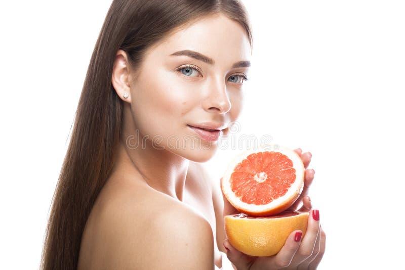 Den härliga unga flickan med ett ljust naturligt smink och gör perfekt hud med grapefrukten i hennes hand Härlig le flicka fotografering för bildbyråer