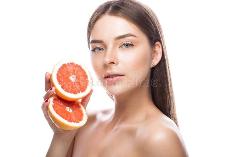 Den härliga unga flickan med ett ljust naturligt smink och gör perfekt hud med grapefrukten i hennes hand Härlig le flicka royaltyfria bilder