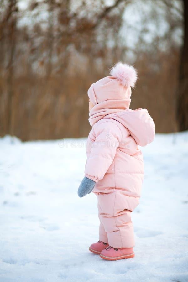 Den härliga unga flickan som bär den rosa romperen som spelar i en snöig vinter, parkerar Barn som spelar med insnöad vinter royaltyfri fotografi