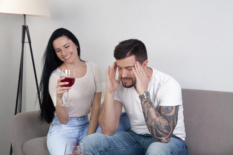 Den härliga unga flickan som dricker vin som sitter på soffan och hennes pojkvän är att sitta som är frustrerat Han har en huvudv royaltyfria foton