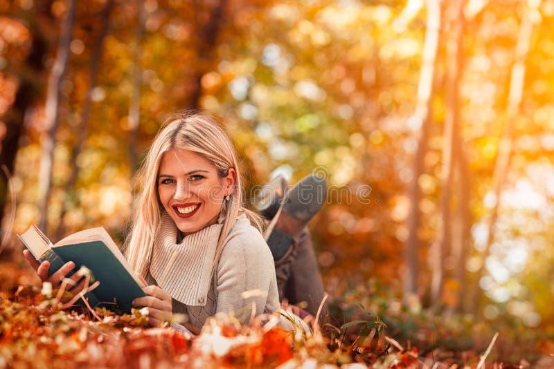 Den härliga unga flickan som läser en bok i höst, parkerar royaltyfri bild