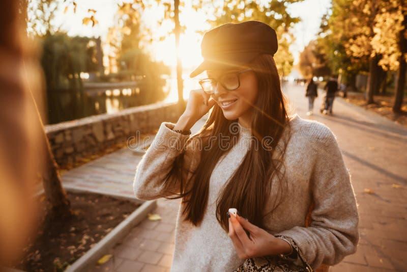 Den härliga unga flickan som lyssnar till musik i, parkerar till och med en trådlös skalm royaltyfria bilder