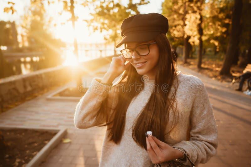 Den härliga unga flickan som lyssnar till musik i, parkerar till och med en trådlös skalm fotografering för bildbyråer