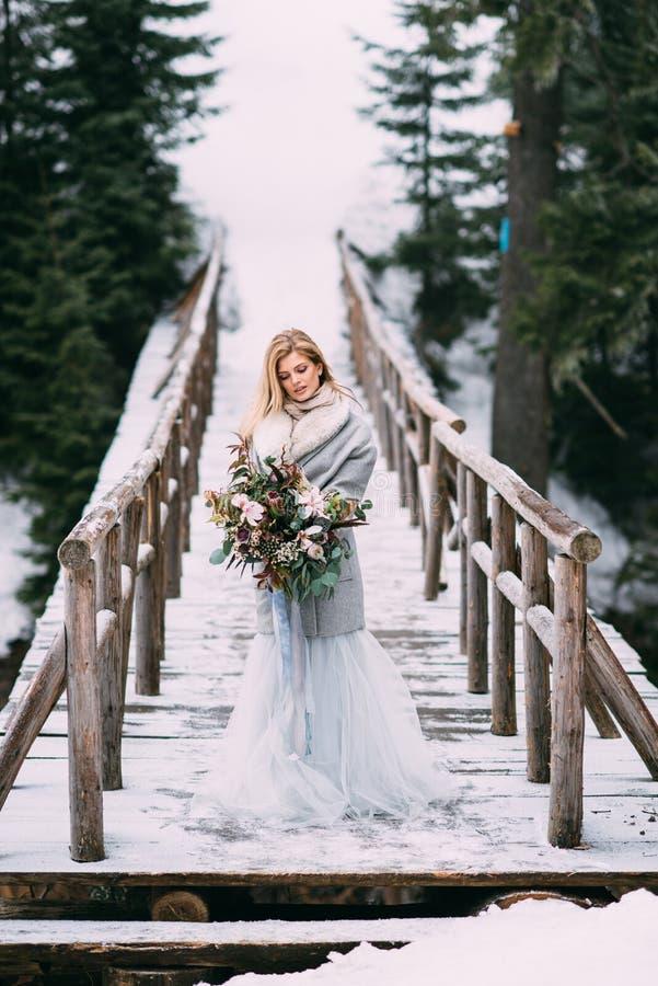 Den härliga unga flickan står i vinter med en bukett av blommor i hennes händer royaltyfria bilder