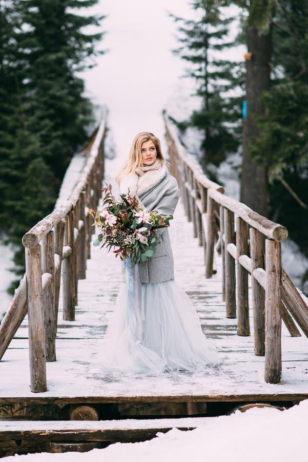 Den härliga unga flickan står i vinter med en bukett av blommor i hennes händer royaltyfri bild
