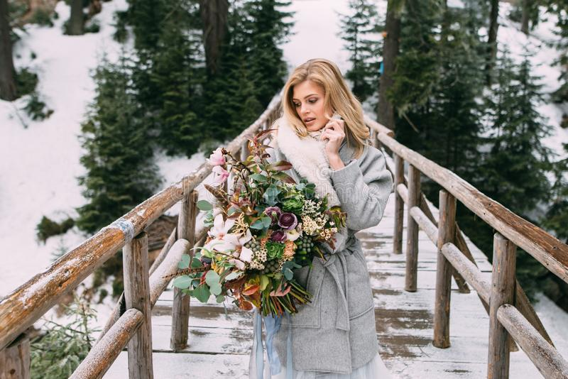Den härliga unga flickan står i vinter med en bukett av blommor i hennes händer fotografering för bildbyråer