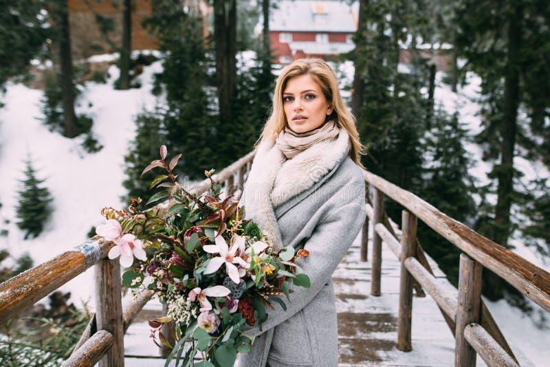 Den härliga unga flickan står i vinter med en bukett av blommor i hennes händer arkivbild