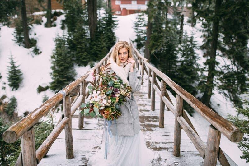Den härliga unga flickan står i vinter med en bukett av blommor i hennes händer royaltyfri fotografi