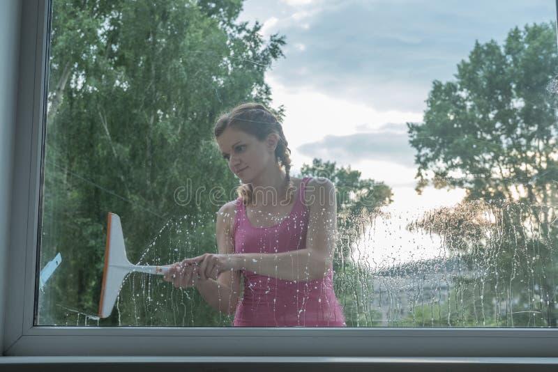 Den härliga unga flickan tvättar ett fönster i ett tegelstenhus arkivbilder