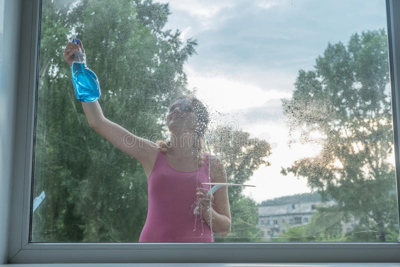 Den härliga unga flickan tvättar ett fönster i ett tegelstenhus royaltyfri bild
