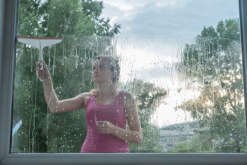 Den härliga unga flickan tvättar ett fönster i ett tegelstenhus arkivfoto