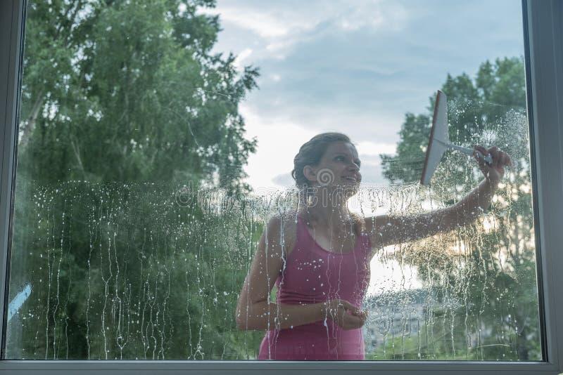 Den härliga unga flickan tvättar ett fönster i ett tegelstenhus arkivbild