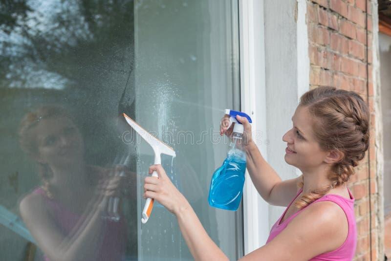 Den härliga unga flickan tvättar ett fönster i ett tegelstenhus royaltyfria bilder