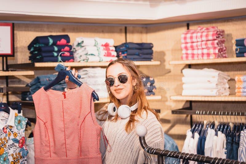 Den härliga unga flickan väljer kläder på mode, och kläder shoppar arkivbilder