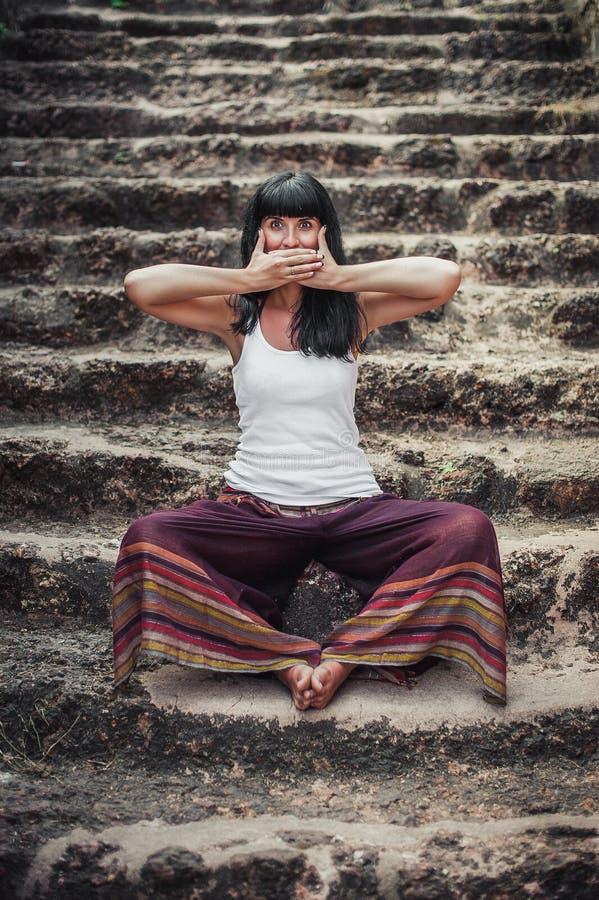 Den härliga unga flickan visar symbol för tre apa arkivfoto