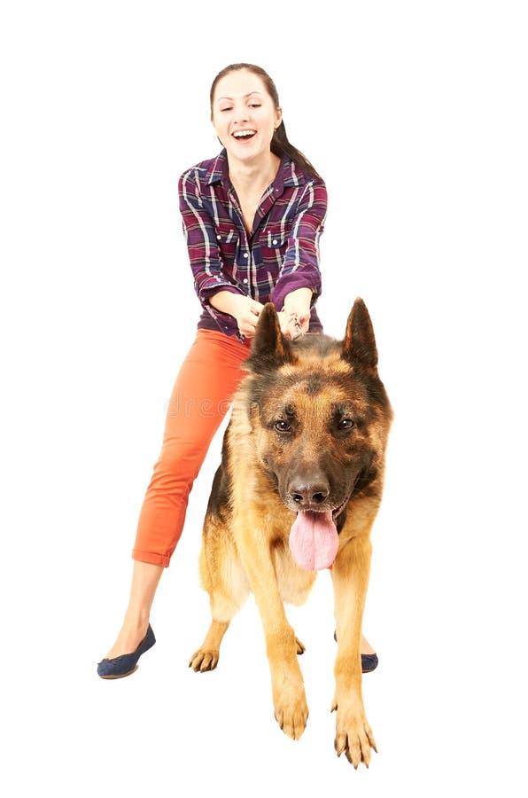 Den härliga unga gladlynta kvinnan rymmer på en tysk herde för ledning royaltyfri foto