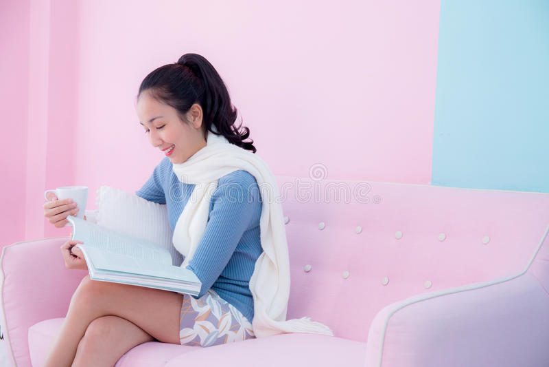 Den härliga unga kvinnan är läseboken och innehavet per koppen kaffe royaltyfria bilder