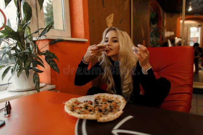 Den härliga unga kvinnan äter en läcker pizza på pizzerian royaltyfri bild