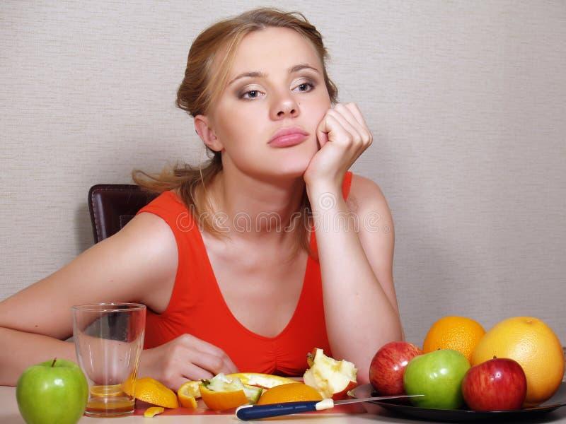 Den härliga unga kvinnan äter frukt royaltyfria bilder