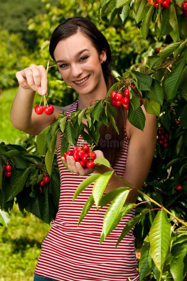 Den härliga unga kvinnan äter körsbäret på koloni arkivbilder