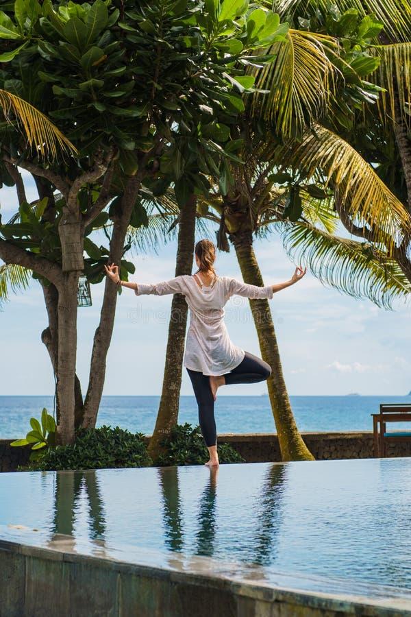 Den härliga unga kvinnan öva yoga, meditationen, anseende poserar på ett ben på pölen med landskap av havet i Indonesien royaltyfri foto