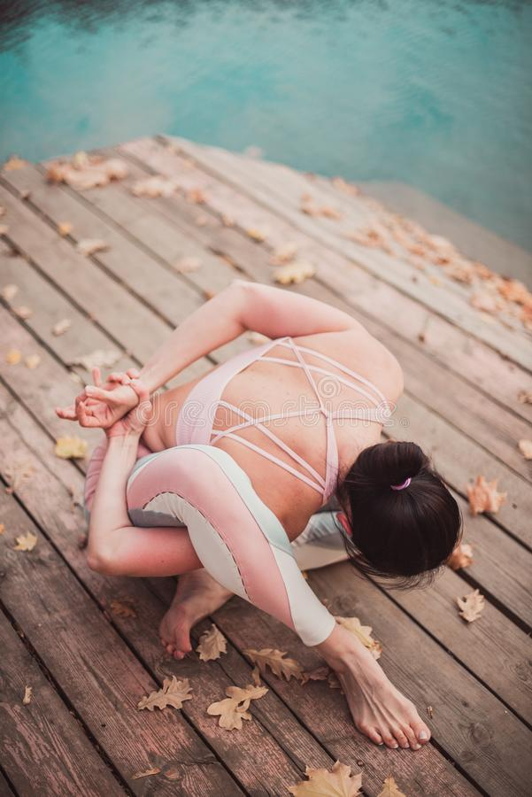 Den härliga unga kvinnan öva yogaasana på träskrivbordet i hösten parkerar royaltyfri foto