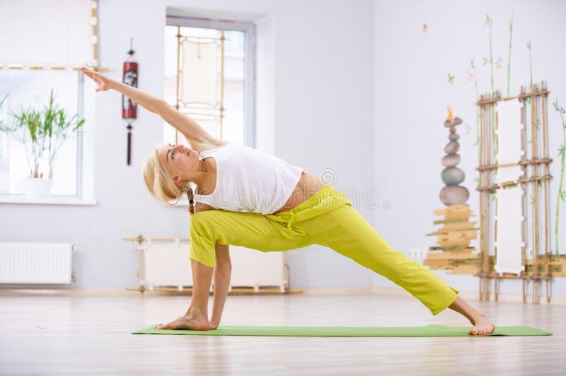 Den härliga unga kvinnan öva yogaasanaen Parivritta Parshvakonasana - kretsa sidovinkel posera i yogagruppen arkivfoto