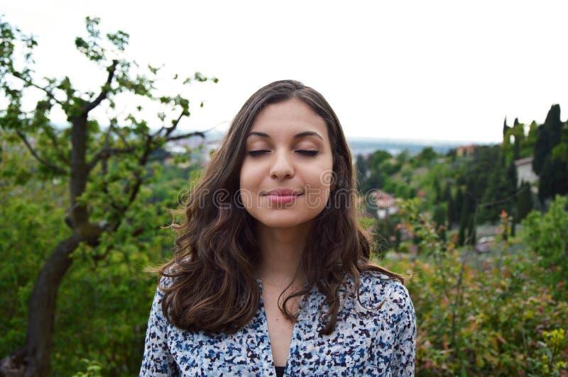 Den härliga unga kvinnan andas med stängda ögon som tycker om den stillsamma andliga reflexionen för tystnadtystnaden royaltyfri bild