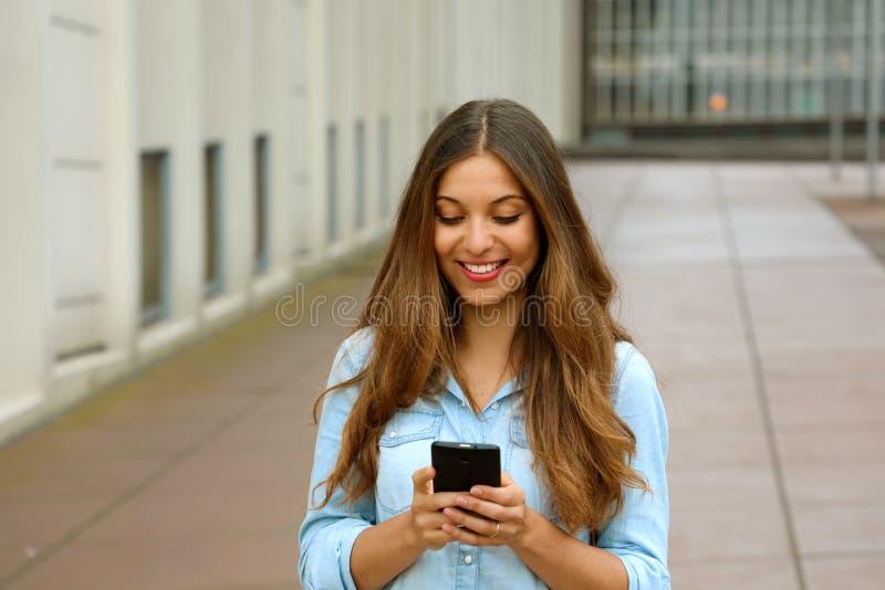 Den härliga unga kvinnan använder en app i hennes smartphoneapparat för att överföra ett textmeddelande, medan stå i borggård av  fotografering för bildbyråer