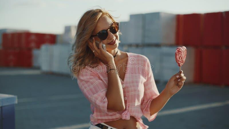 Den härliga unga kvinnan använder en smartphone på gatan och slickar den kulöra klubban arkivfoto