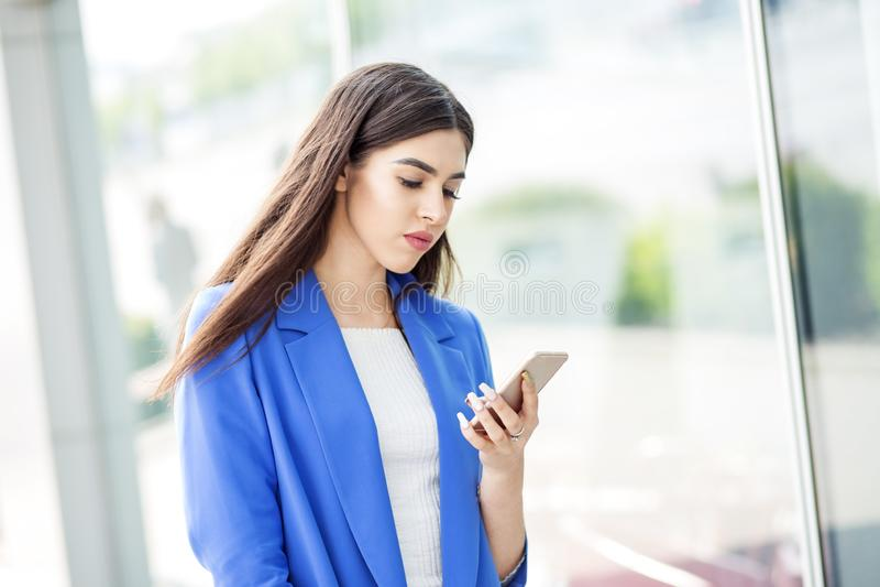 Den härliga unga kvinnan använder internet på telefonen Begreppet av mode, affären, kommunikationen och livsstilen royaltyfri foto
