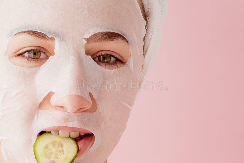 Den härliga unga kvinnan applicerar en kosmetisk silkespappermaskering på en framsida på en rosa bakgrund Sjukvård- och skönhetbe arkivfoton