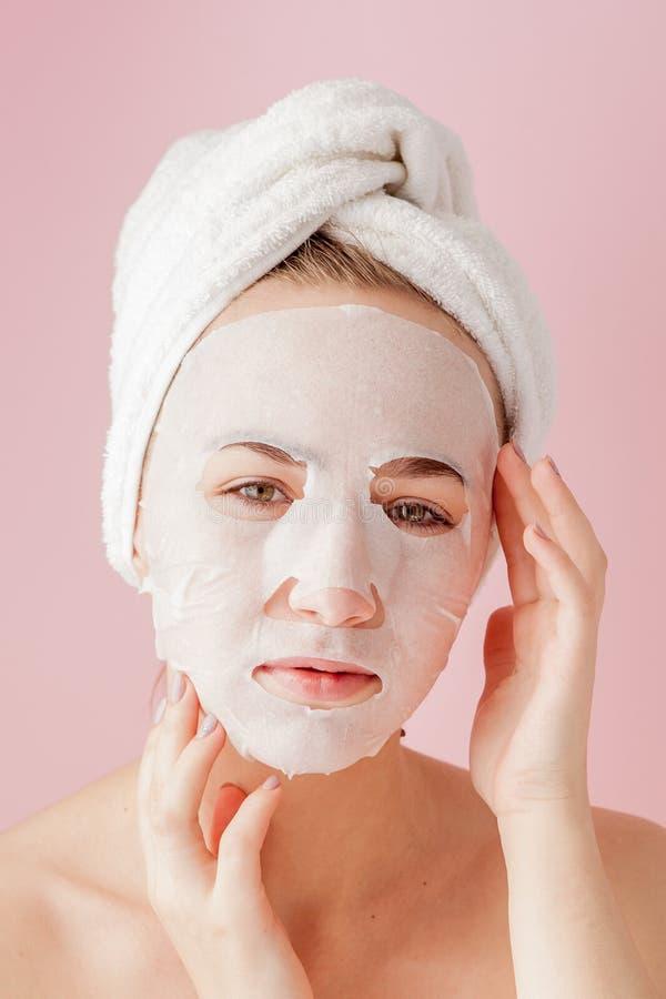 Den härliga unga kvinnan applicerar en kosmetisk silkespappermaskering på en framsida på en rosa bakgrund Sjukvård- och skönhetbe royaltyfria bilder