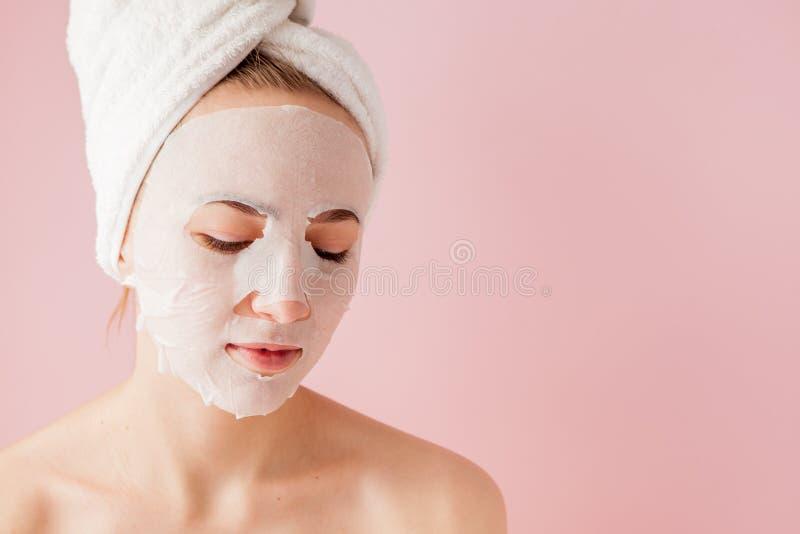 Den härliga unga kvinnan applicerar en kosmetisk silkespappermaskering på en framsida på en rosa bakgrund Sjukvård- och skönhetbe fotografering för bildbyråer