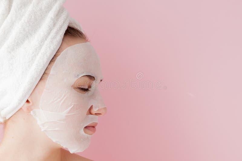 Den härliga unga kvinnan applicerar en kosmetisk silkespappermaskering på en framsida på en rosa bakgrund Sjukvård- och skönhetbe royaltyfri foto