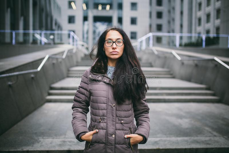 Den härliga unga kvinnan av europeisk etnicitet med långt brunetthår, bärande exponeringsglas och ett lag står mot bakgrunden av  royaltyfri foto