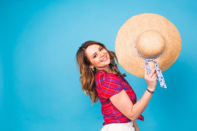 Den härliga unga kvinnan bär i sommarklänning, och sugrörhatten skrattar på blå bakgrund med kopieringsutrymme royaltyfria foton