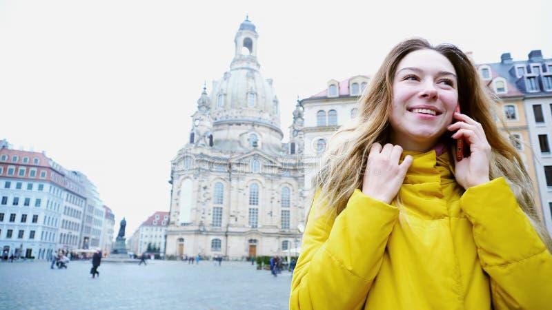 Den härliga unga kvinnan berättar vid telefonen om oerhört intryck royaltyfria foton