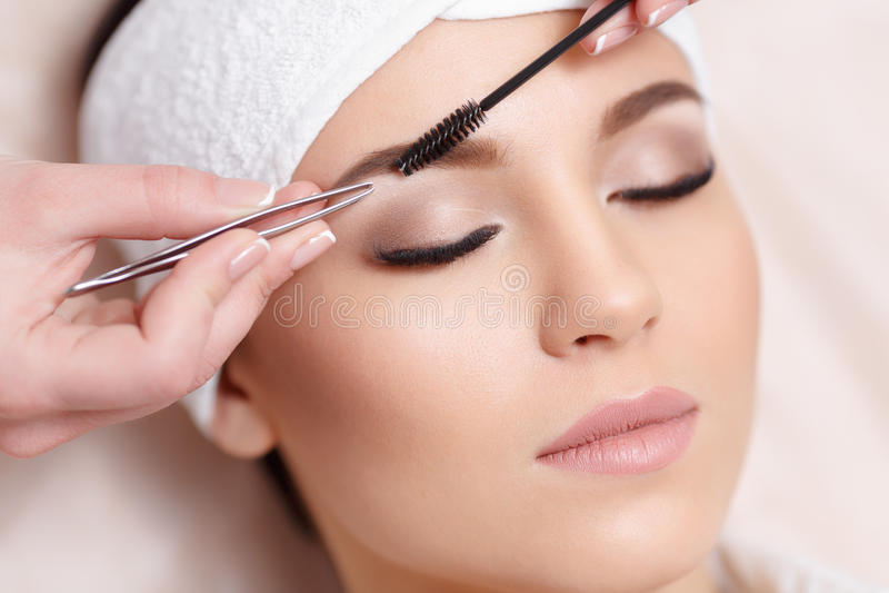 Den härliga unga kvinnan får ögonbrynkorrigeringstillvägagångssätt royaltyfri fotografi