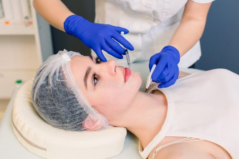 Den härliga unga kvinnan får en injektion i hennes kanter, närbilden, sidofoto Ung kvinna som f?r kantinjektionen fotografering för bildbyråer