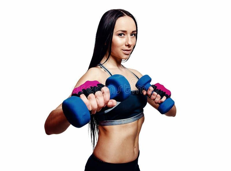 Den härliga unga kvinnan gör övningar med hantlar i studio Sportig idrotts- flicka som lyfter upp vikter mot vit bakgrund royaltyfri fotografi