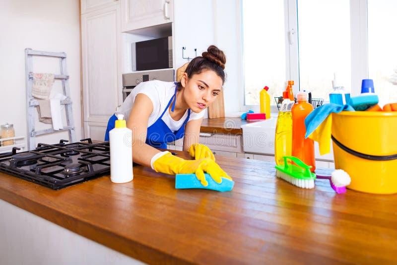 Den härliga unga kvinnan gör att göra ren huset Flickalokalvårdki arkivfoton