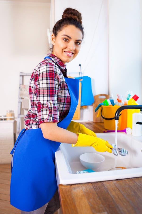 Den härliga unga kvinnan gör att göra ren huset Flickalokalvårdki fotografering för bildbyråer