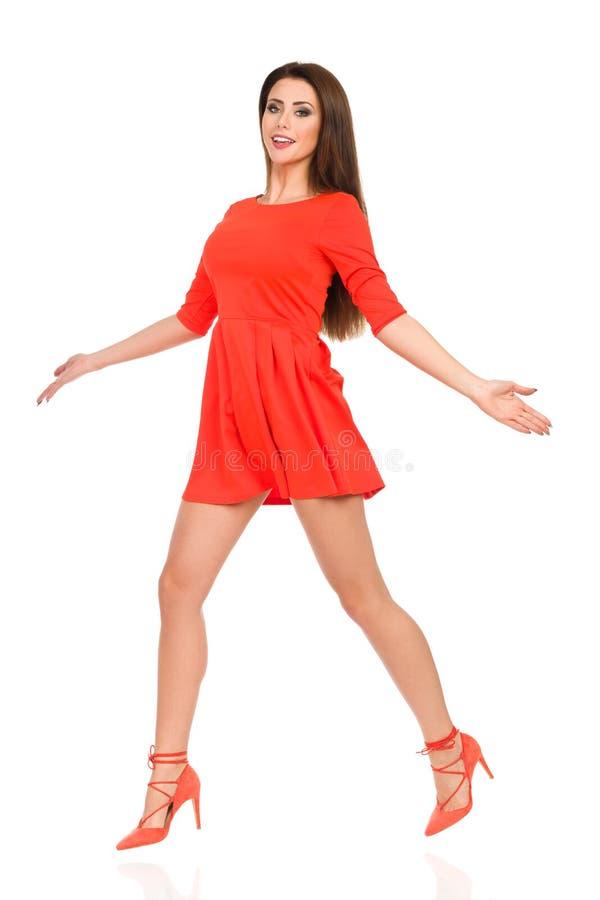 Den härliga unga kvinnan hoppar i röda Mini Dress And High Heels royaltyfri fotografi