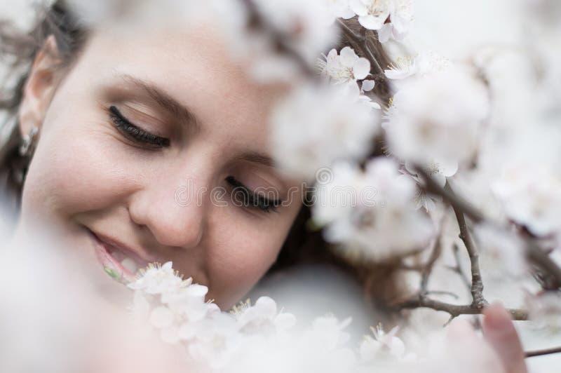 Den härliga unga kvinnan, i att blomma körsbärsröda blomningar, arbeta i trädgården royaltyfri bild