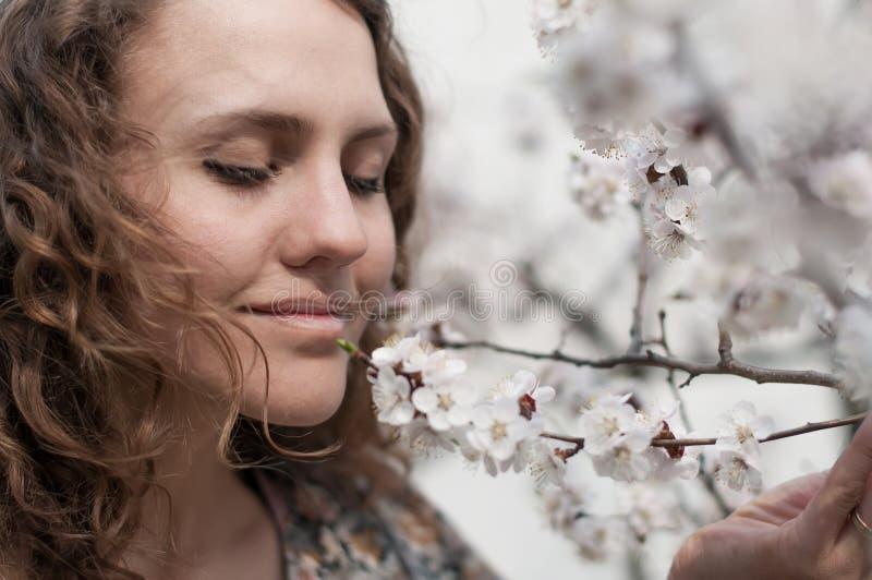 Den härliga unga kvinnan, i att blomma körsbärsröda blomningar, arbeta i trädgården royaltyfria foton