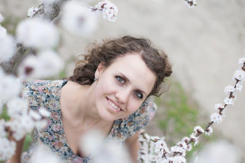 Den härliga unga kvinnan, i att blomma körsbärsröda blomningar, arbeta i trädgården royaltyfri fotografi