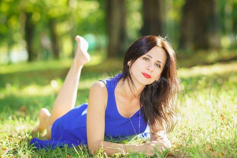 Den härliga unga kvinnan i blått klär att ligga på gräset arkivfoto
