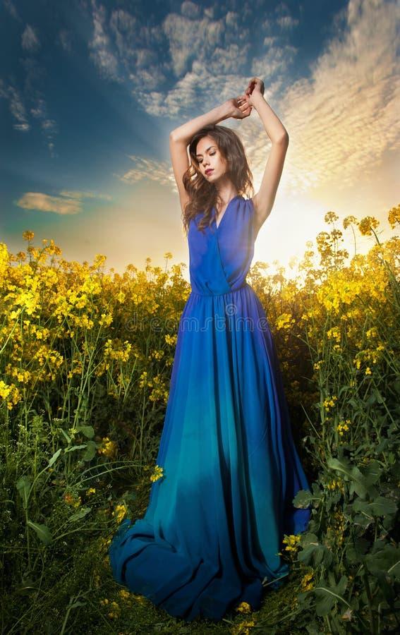 Den härliga unga kvinnan i blått klär att posera som är utomhus- med molnig dramatisk himmel i bakgrund fotografering för bildbyråer